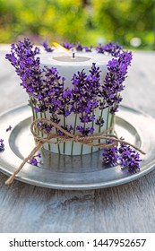 white  burning candle decorated with lavender on pewter plate