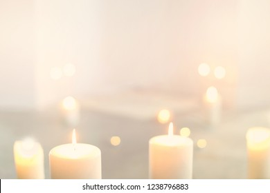 White burning candles in front with soft-focused candlelights on background in light empty room