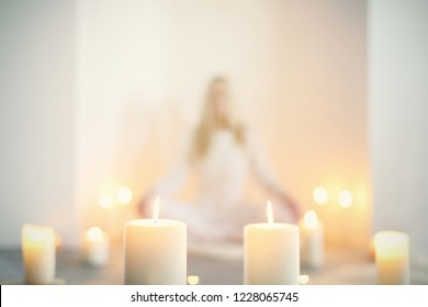 White burning different sized candles in front with soft-focus lady sitting on the floor in peaceful position in the background in a light and very peaceful atmosphere