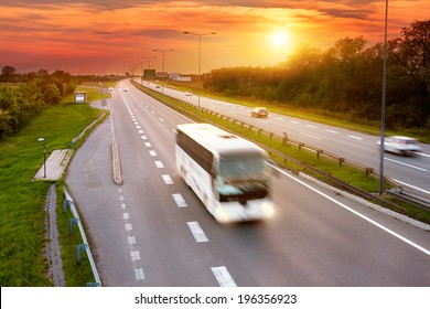 White bus in the rush hour on the highway at dusk
