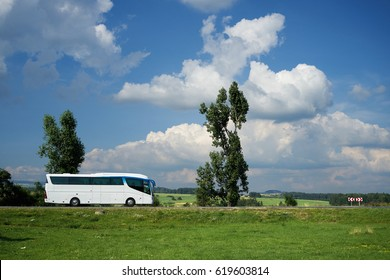 The white bus traveling on the road next to tall trees in a rural landscape under a blue sky with dramatic white clouds