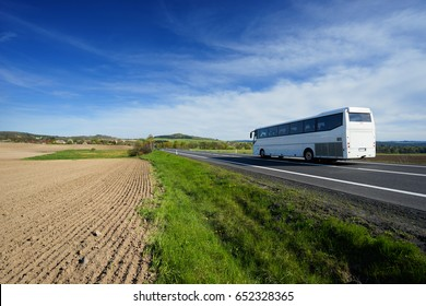 The white bus traveling on the road around a sown field in a rural landscape with a village in the background