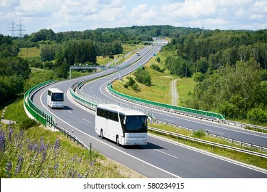 White buses driving on the highway winding through forested areas. View from above.