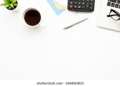 White business office desk table with laptop computer, business graph documents, cup of coffee, and supplies. Top view with copy space, flat lay.