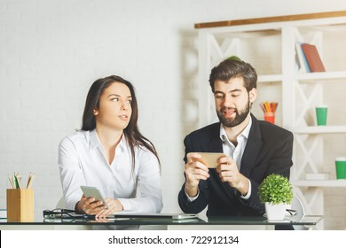 White businessman and woman using smartphone at modern office workplace. Leisure, break, distraction, social media, technology and communication concept