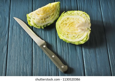 White cabbage slices with knife on the blue wooden background