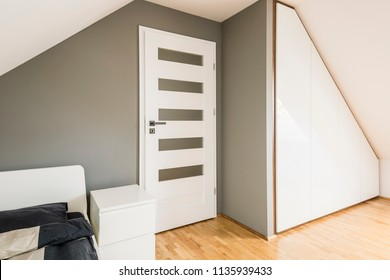 White cabinet between white door and bed with sheets in grey bedroom interior on attic. Real photo