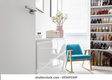 White cabinets in elegant classic walk-in closet with open storage for shoes, door, blue vintage armchair and pastel decor