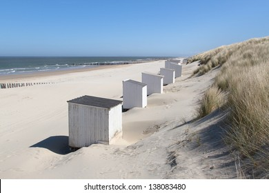 White cabins (or beach houses) standing against the grass covered dunes on a deserted beach at Domburg in Holland.