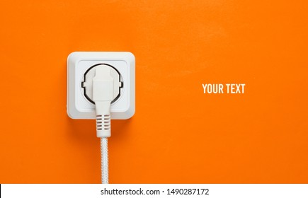 White cable plugged into power outlet on orange wall background with copy space