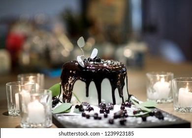 White cake with chokolate topping, berries, flour, candles and eucalyptus leaves around