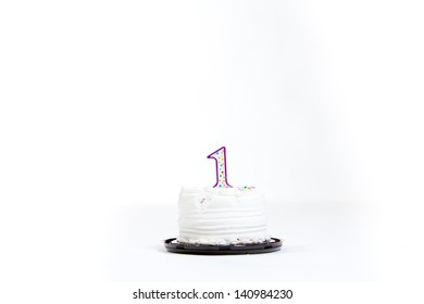 A white cake isolated against a white background in the studio for a baby first birthday.