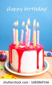 White cake with red icing and candles on a blue background. Birthday concept.