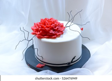 White cake with red rose, branches and black belt