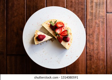 white cake stand sitting on wooden floor holds slices of vanilla cheesecake garnished with strawberries