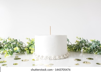 White cake with topper stick and blank background space with confetti and greenery props, cake topper mockup