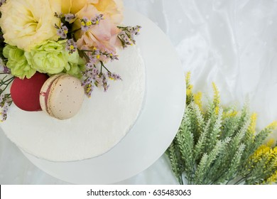 white cake topping with macaroon and beautiful flower. close up