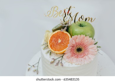 white cake topping with orange, green apple and pink flower. close up