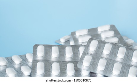 White calcium pills isolate on blue background in transparent blister pack,Calcium carbonate supplement for calcium insufficiency patients and good for bone health, copy space for text,selective focus