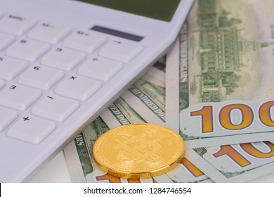 white calculator and bitcion golden coin on 100 dollars banknotes