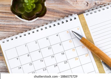 white calendar for 2021 month schedule to make an appointment or manage the schedule every day on a wooden table with succulent and ballpoint pen for marks, for work planning