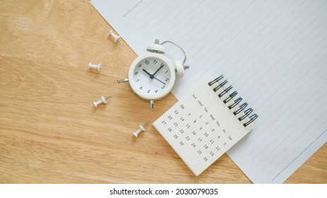 white calendar, thumbtack and analog alarm clock on school paper with line on wooden desk for back to school concept