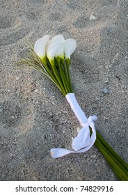 white calla lilies laying on sand