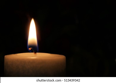 White Candle Against Dark Background - photograph of a lit white candle against a plain dark background.  Plenty of room for text.