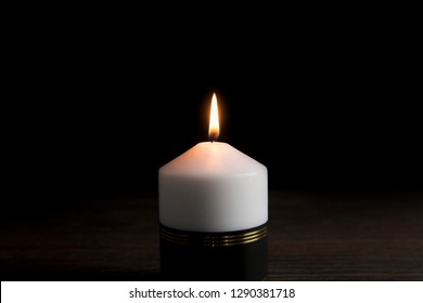 White candle with black ribbon, symbol of remembrance or mourning, black background. Lot of blank copy space for your text.