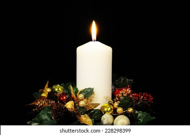 White candle and Christmas flowers against a black background.