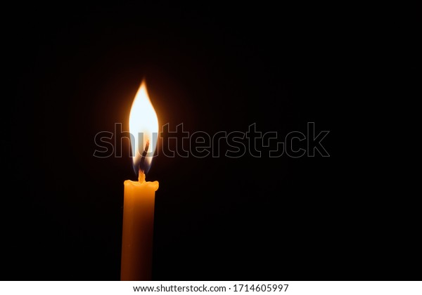 White candle flame closes upon a black background, Candle Burning in the Dark with lights glow, The burning candle's flame with light glow background a symbol of the Christian faith.