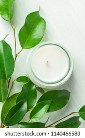 White Candle in Glass Jar Fresh Tree Branches with Tender Green Leaves on Wood Background. Spa Wellness Body Care Meditation Concept. Minimalist Scandinavian Style. Copy Space. Top View