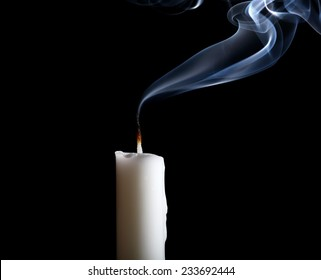 White candle isolated on black background.