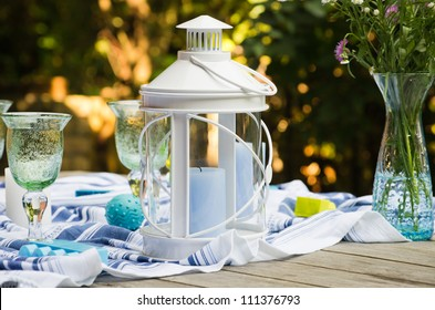 White candle lantern on a served wooden table with goblets and a vase with flowers