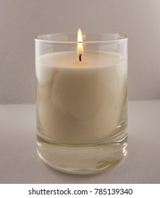 white candle in a large transparent glass