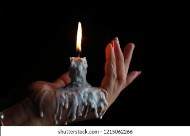 White Candle melted on hand in black background. For halloween's concept. Felling darkness with light of flame burning from the supernatural.
