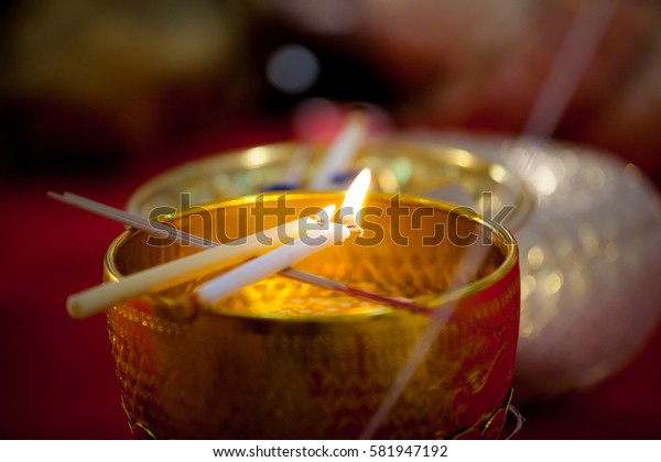 White candle melting on brass bowl for make holy water in wedding ceremony
