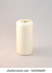 A white candle on a light gray background.