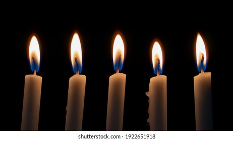 White Candles Burning in the Dark with lights glow. The burning candle's flame in the dark background. a symbol of the Christian faith. Candles Burning in the Dark with lights glow.White Candles