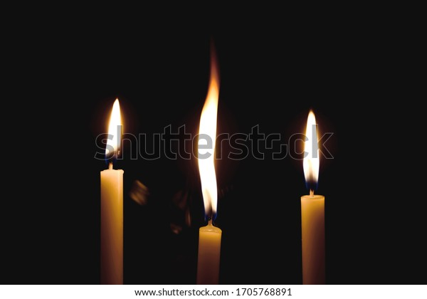White Candles Burning in the Dark with lights glow. The burning candle's flame in the dark background. a symbol of the Christian faith. Candles Burning in the Dark with lights glow.