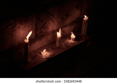 White candles in the candlesticks, pots and jars for meditation and relaxtaion in an abandoned house. Shamanic rituals for meditation in abandoned place.