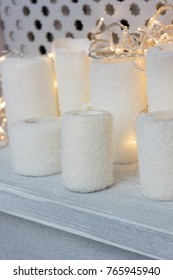 White candles with christmas lights as decoration for new year.