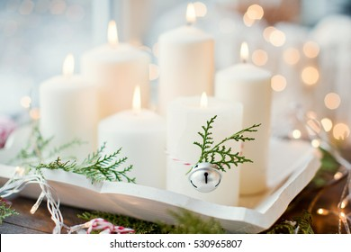 white candles, jingle bells and twigs of thuja