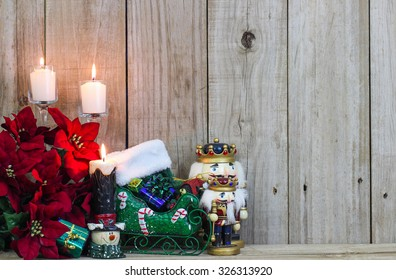 White candles, red poinsettias and Christmas decor by rustic antique wooden background