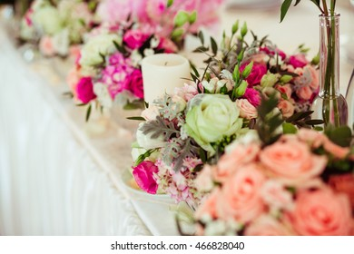 White candles stand among pink peonies on the dinner table