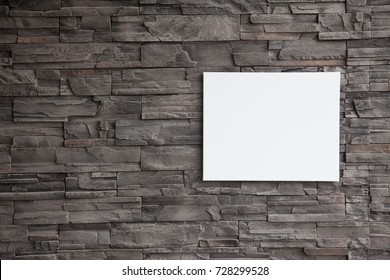 white canvas frame holding on rock wall