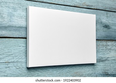 White canvas hanging on light blue wooden wall. Mockup, wall decor, blank canvas stretched on stretcher bar, side view - Shutterstock ID 1922403902