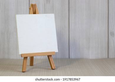 White canvas on a small easel on a light wooden background, close up, blank sheet concept with copy space