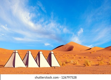White canvas portable shower and toilet enclosures in a Sahara desert camp. Colorful image with orange sand dunes and blue sky with swirling clouds. Adventure travel.
