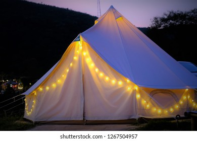 White canvas tent Decorated with glowing yellow lights. Outdoor camping concept in resort. Ecotourism traveling concept. Evening and twilight concept.